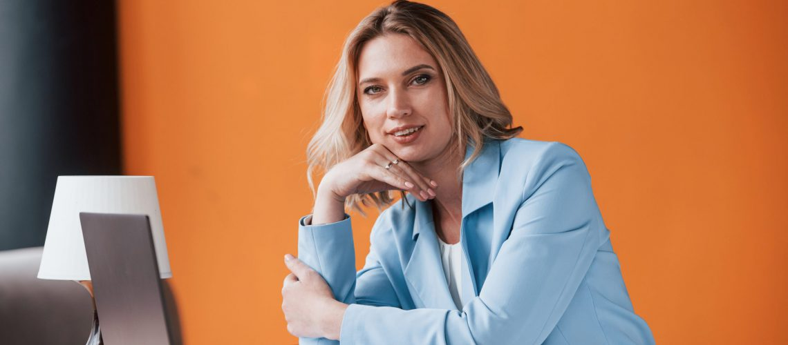 If you need advice, I can help. Businesswoman with curly blonde hair indoors in room with orange colored wall and wooden table.